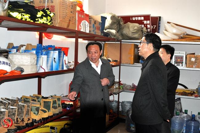 县林业局局长王洲向侯怀堂一行介绍防火器材的储备情况。