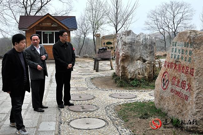 侯怀堂(右一)在查看森林防火重点区域的防范措施。
