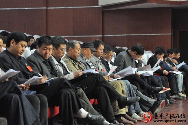 政协委员们在认真听取政协工作报告。