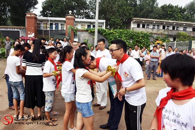 李兴楼小学的学生为思考乐教育集团嘉宾佩戴红领巾。