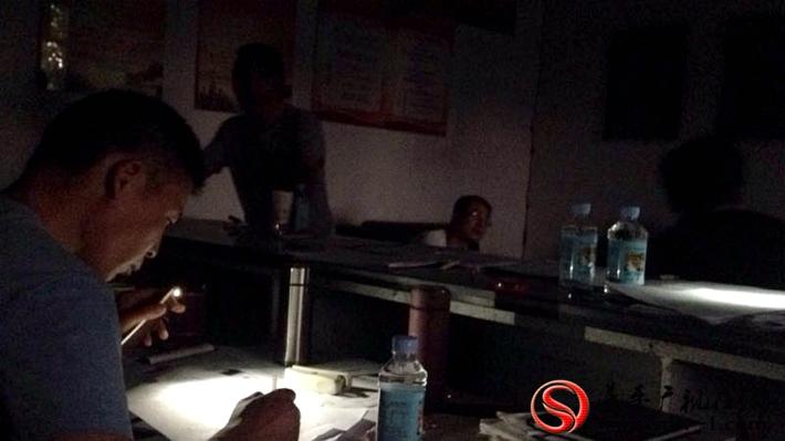 图为:夜间停电镇村干部用手机照亮整理材料。