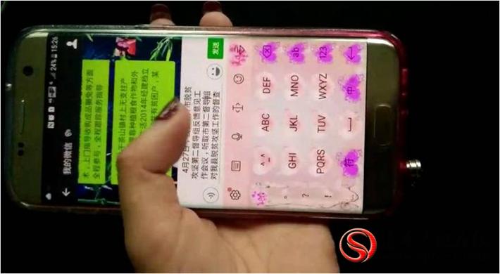 图为:5月19日,因暴雨停电县扶贫办工作人员用手机写材料。