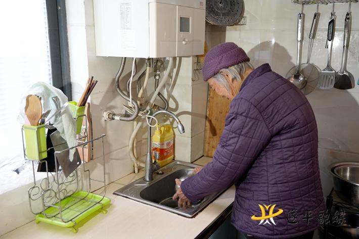 上图:钟玉莲老人在洗碗。